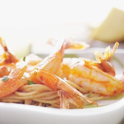A portion of Chili-Lime Shrimp with pasta is served in a white dish.
