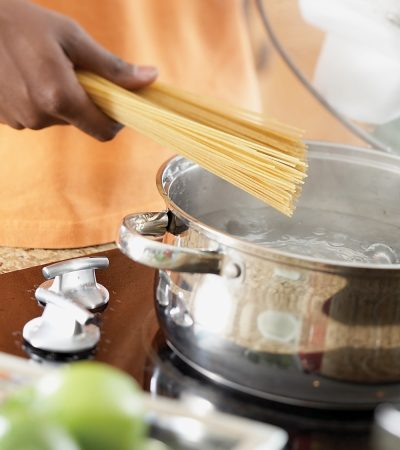 A man places pasta in a pot of boiling water.