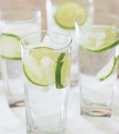 Slices of lime float in glasses of seltzer water.
