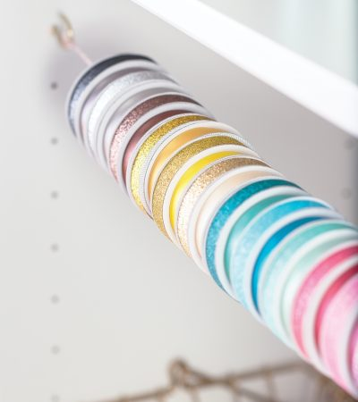 Selecting and cutting wrapping paper and ribbon is most efficient when rolls are easy to access. Thin spools of ribbon can be strung across the width of an organizer with two cup hooks and heavy cord.