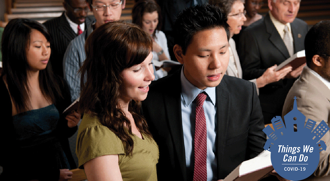 Stock couple singing hymn with covid 19 badge
