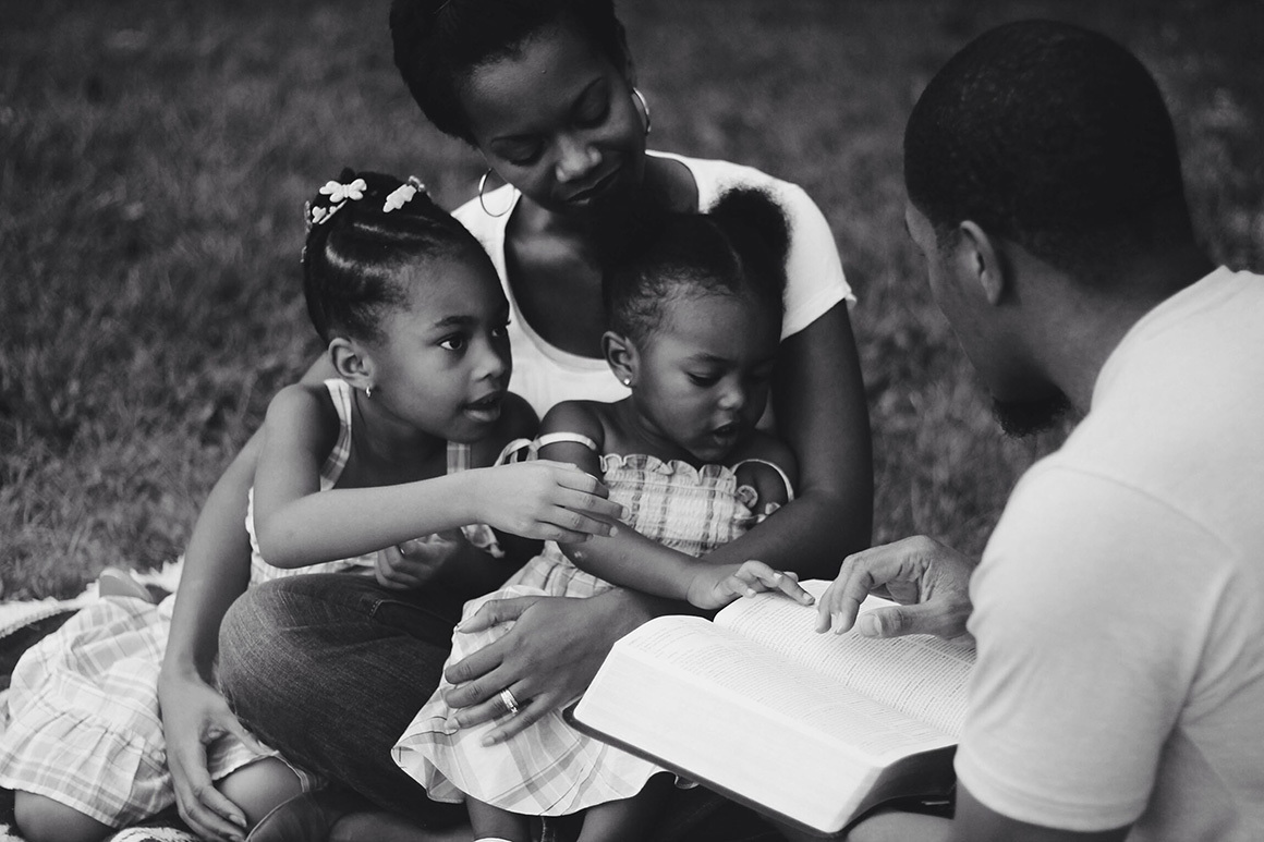 Stock family looking at bible together bw