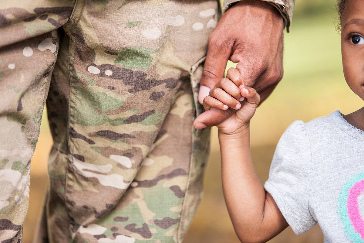 Stock girl holding soldiers hand