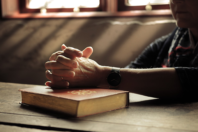 Stock hands clasped over bible