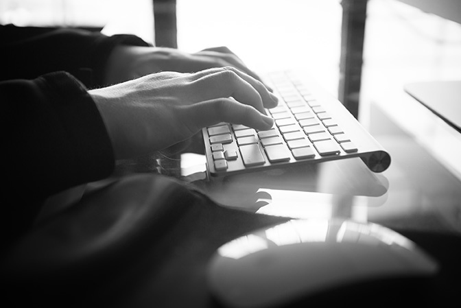 Stock hands typing on keyboard bw
