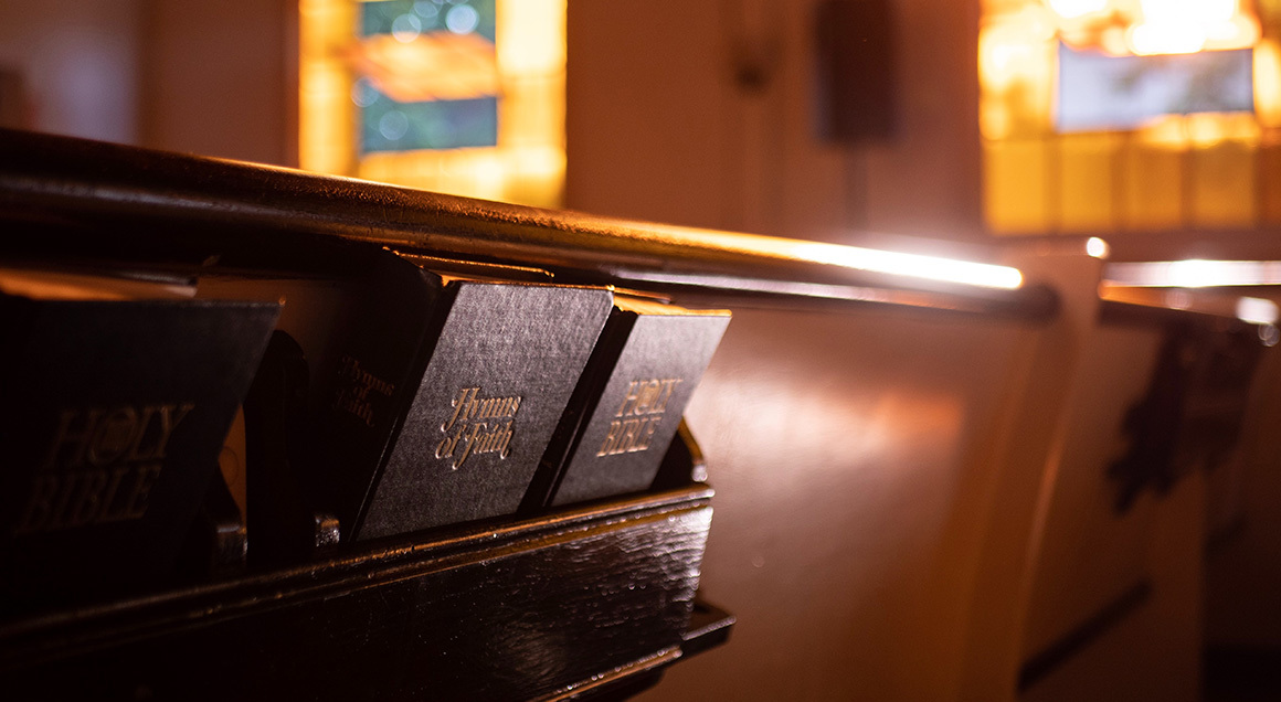 Stock hymnal and bible on back of pew