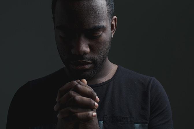 Stock man praying with eyes closed