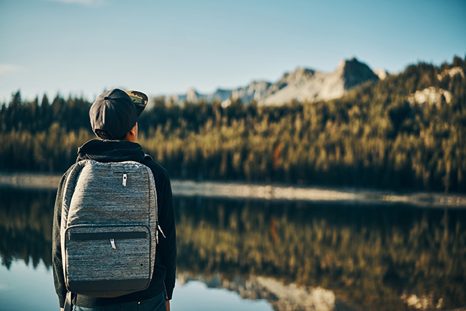Stock man with backpack overlooking lake