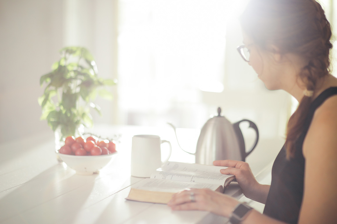 Stock woman reading bible while drinking coffee