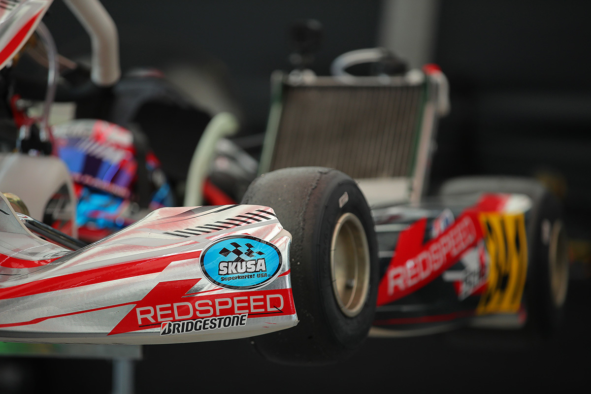 A Redspeed kart sits atop a karting stand with a SKUSA sticker on the front nose