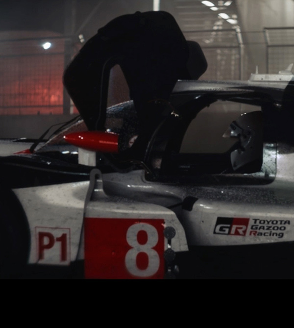 多色曲线的丰田赛车反射着赛道灯光。车手蓄势待发。