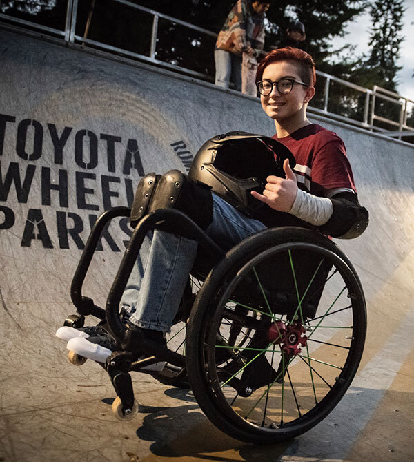 Wheelchair motocross rider Lily Rice smiles at the camera while holding her helmet and throwing the shaka hand sign.