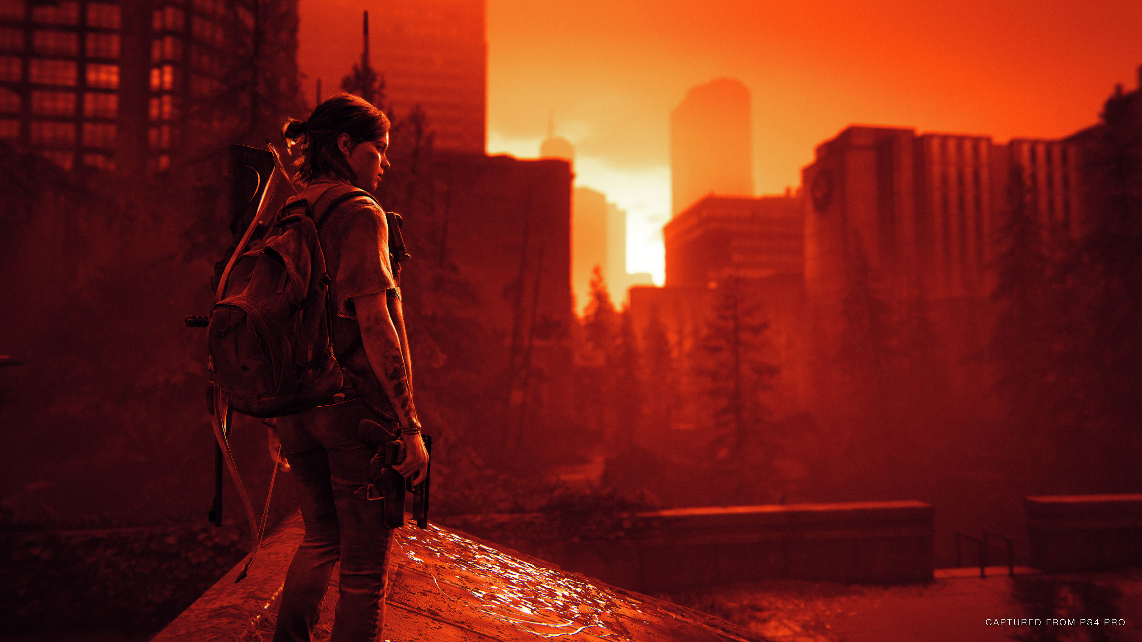 Ellie stands on a rooftop looking out to the hospital with the Inferno render mode over the image.