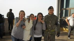 A group of three girls posing with a soldier from the DMZ.