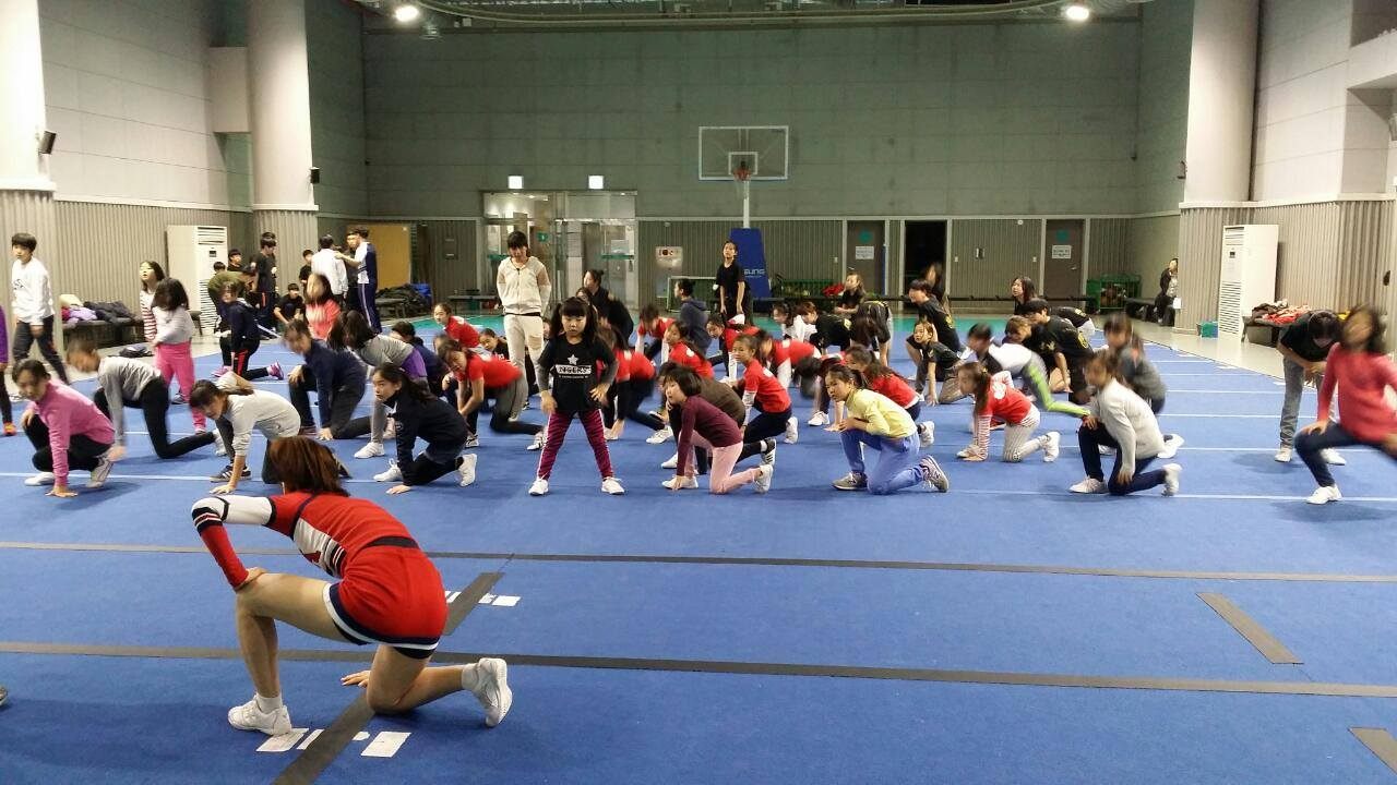 NSLIY cheerleading student leads a group of elementary schools with stretching poses.