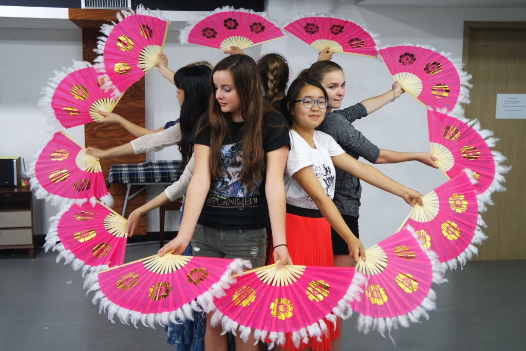 A group of NSLIY girls forming a flower with traditional Korean fans.