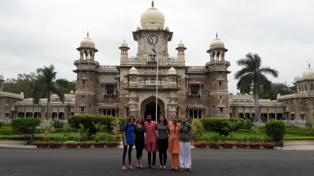 The academic year students in India pose of front of a beautiful building