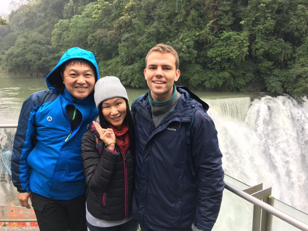 Picture of Anthony with his host family in front of a waterfall