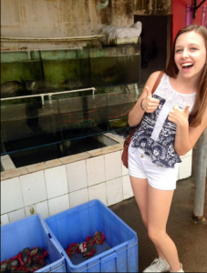 Lauren pictured next to a bin of crawfish