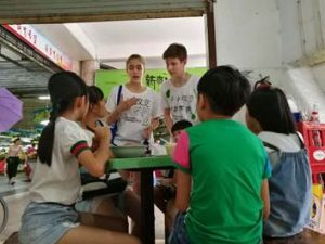NSLI-Y Chinese participants discuss plastic waste with local children.