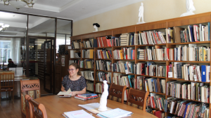 Grace surrounded by books in Grace pictured in Grace and a historian at Kirov Library.