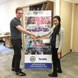 Paula posing with a fellow intern in front of an iEARN banner.