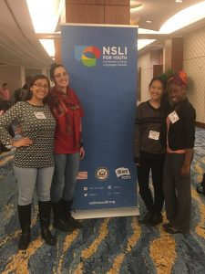 Paula posing with fellow interns in front of a NSLI-Y banner.