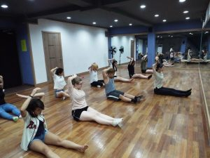 Carlie and her fan dancing team stretching at the studio.