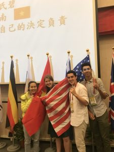 NSLI-Y participants surrounding an American flag at their speech competition.