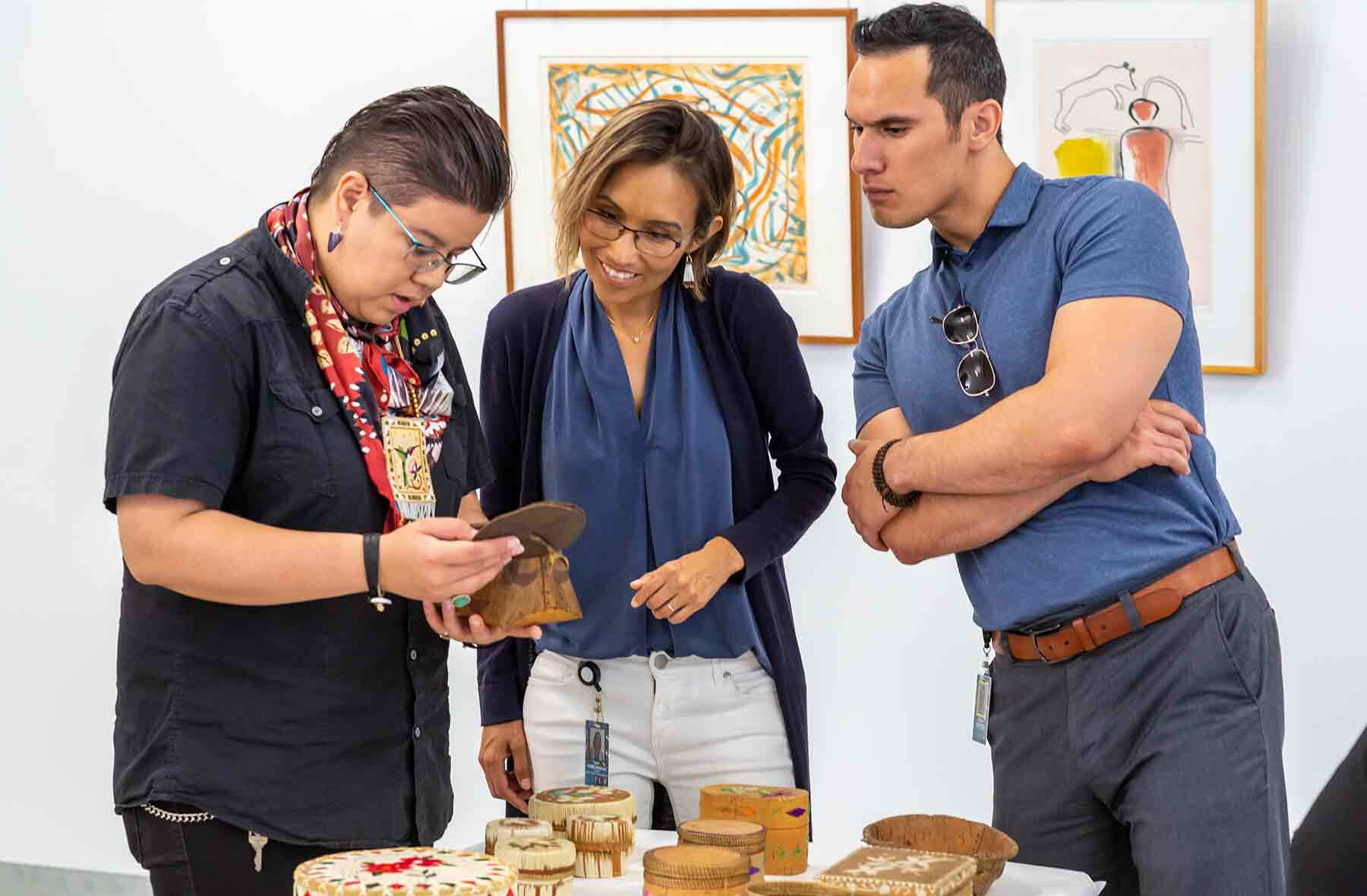 Jennifer Himmelreich (Diné), Native American Fellowship Program Manager (center) looks at objects in collection storage with 2019 summer Fellows Neebinnaukzhik (Neebin) Southall (Chippewa of the Rama First Nation) at left, and Kamuela Werner (Kanaka Maoli) © 2019 Peabody Essex Museum.