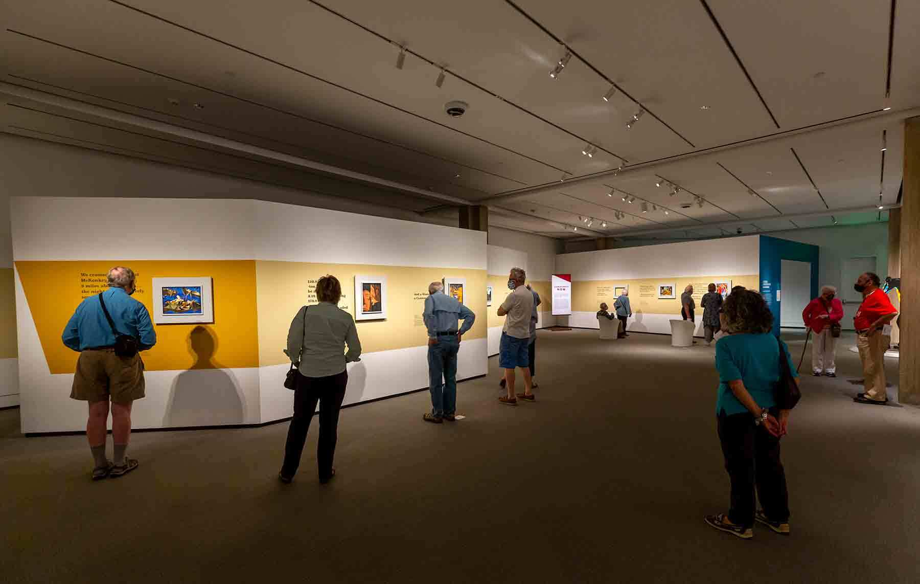 Socially distanced visitors feast their eyes on the paintings of Jacob Lawrence's Struggle series, which is on view at PEM until August 9.