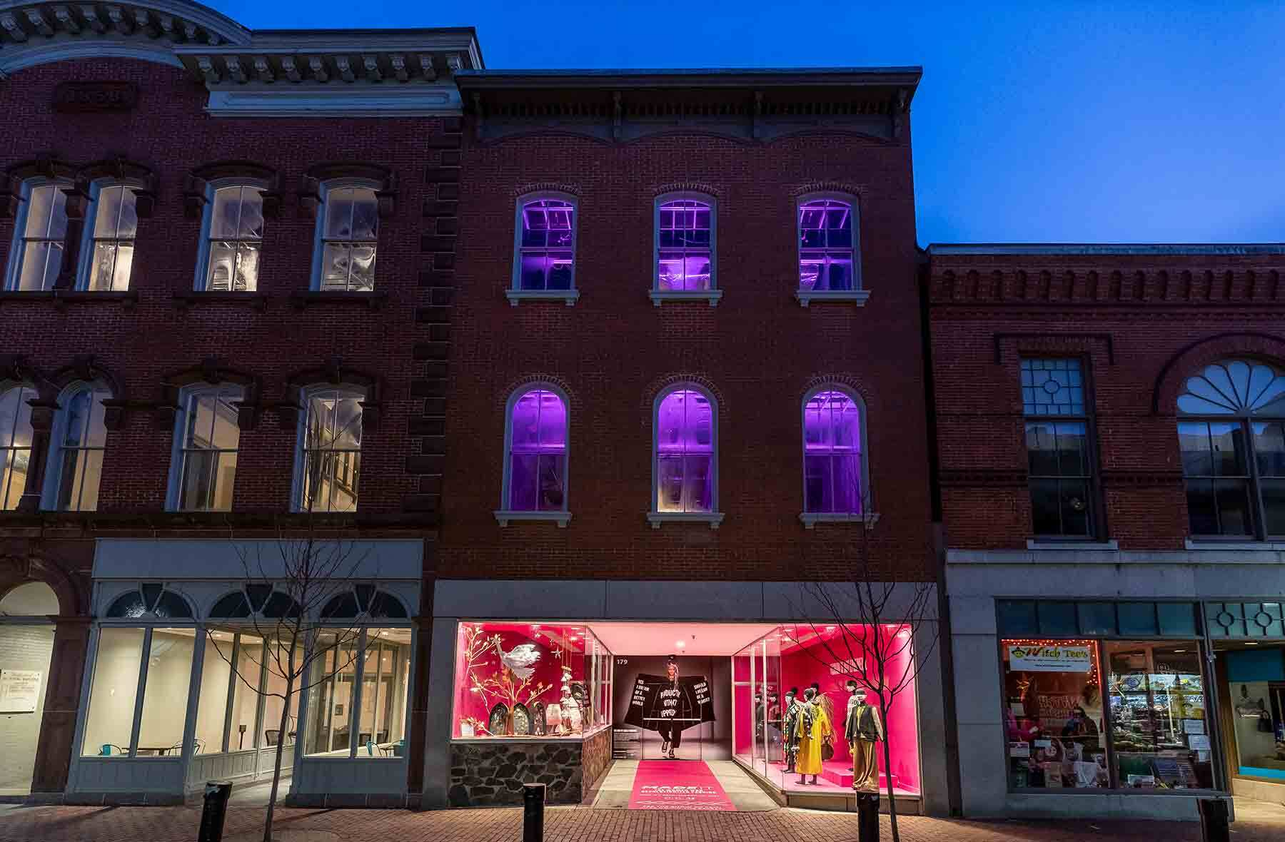 A night time view of a shop window display with pink walls in a brick building.