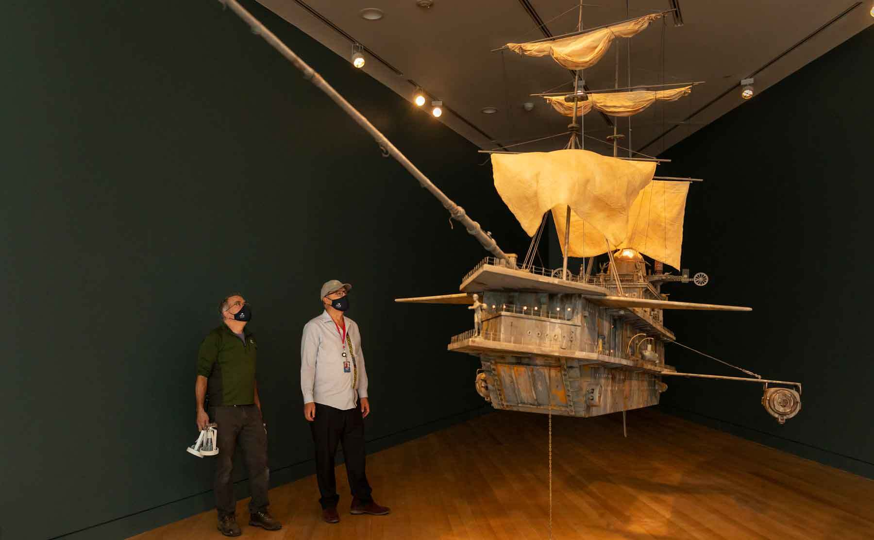 Curator Trevor Smith and Scott Benson next to a work of art carefully lit. Michael C. McMillen. The Pequod II, 1987. Peabody Essex Museum, Gift of Michael and Lauren McMillen, in memory of James Doolin. Photo by Kathy Tarantola