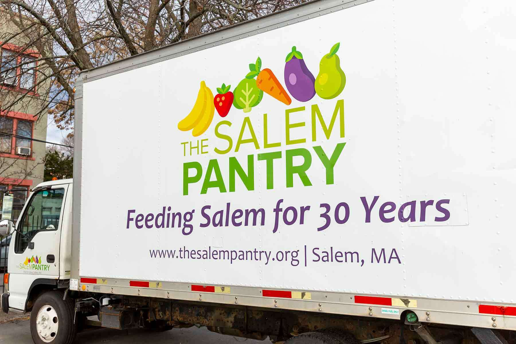 Side view of a white truck with the Salem Pantry logo on it.