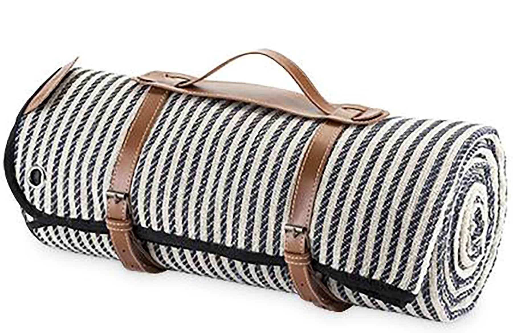 a picnic blanket rolled up with a leather handle and straps
