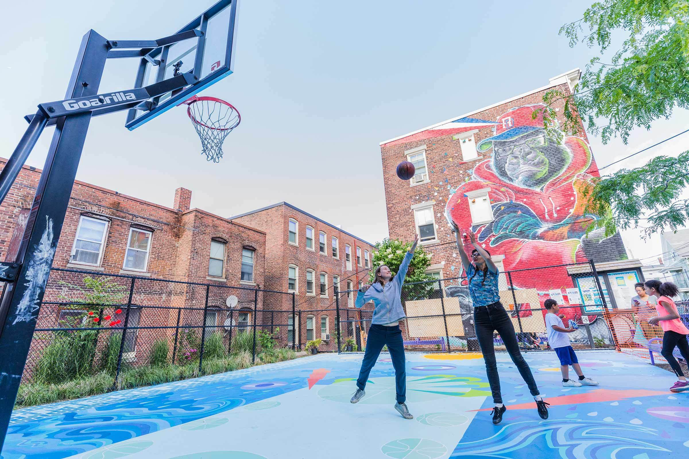 Guest artist Maria Molteni shoots a jump shot on the finished court, a celebration of color, creativity and the rewards of collaboration. Photo by Bob Packert/PEM.