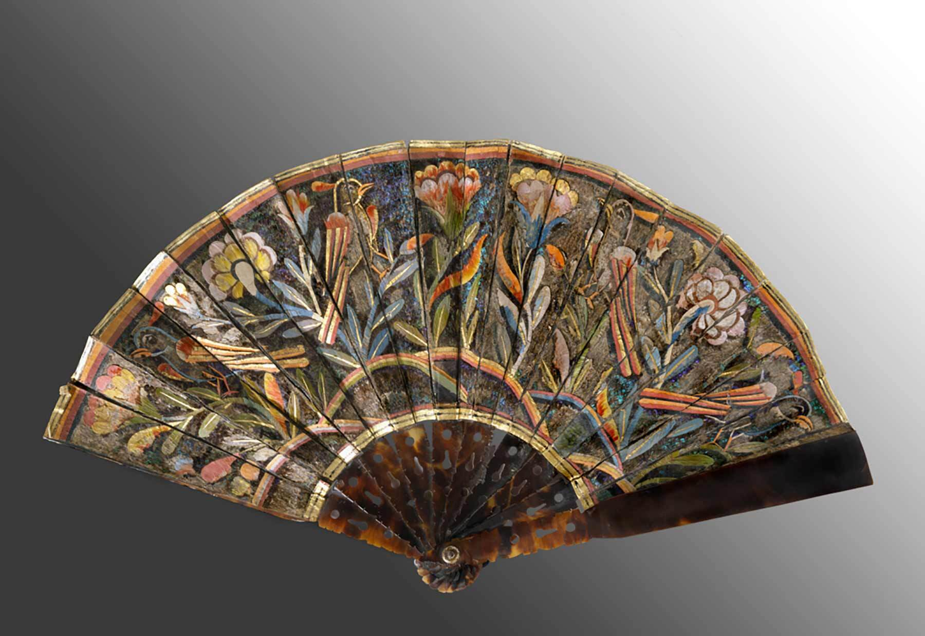 A folding fan comprised of pierced hawksbill tortoise shell, painted paper and feathers, it was created during the first century of the Spanish Colonial Era