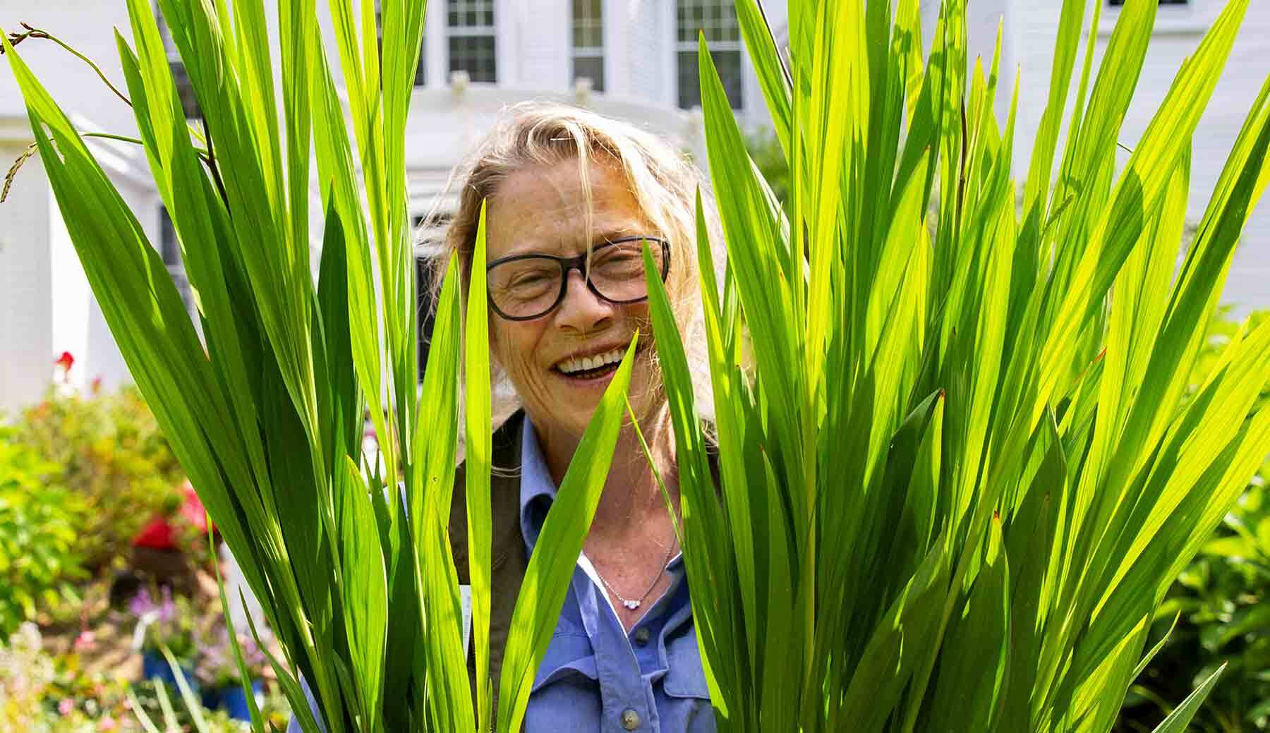 Head Gardener Robin Pydynkowski smiling, looking at viewer through tall green plant leaves