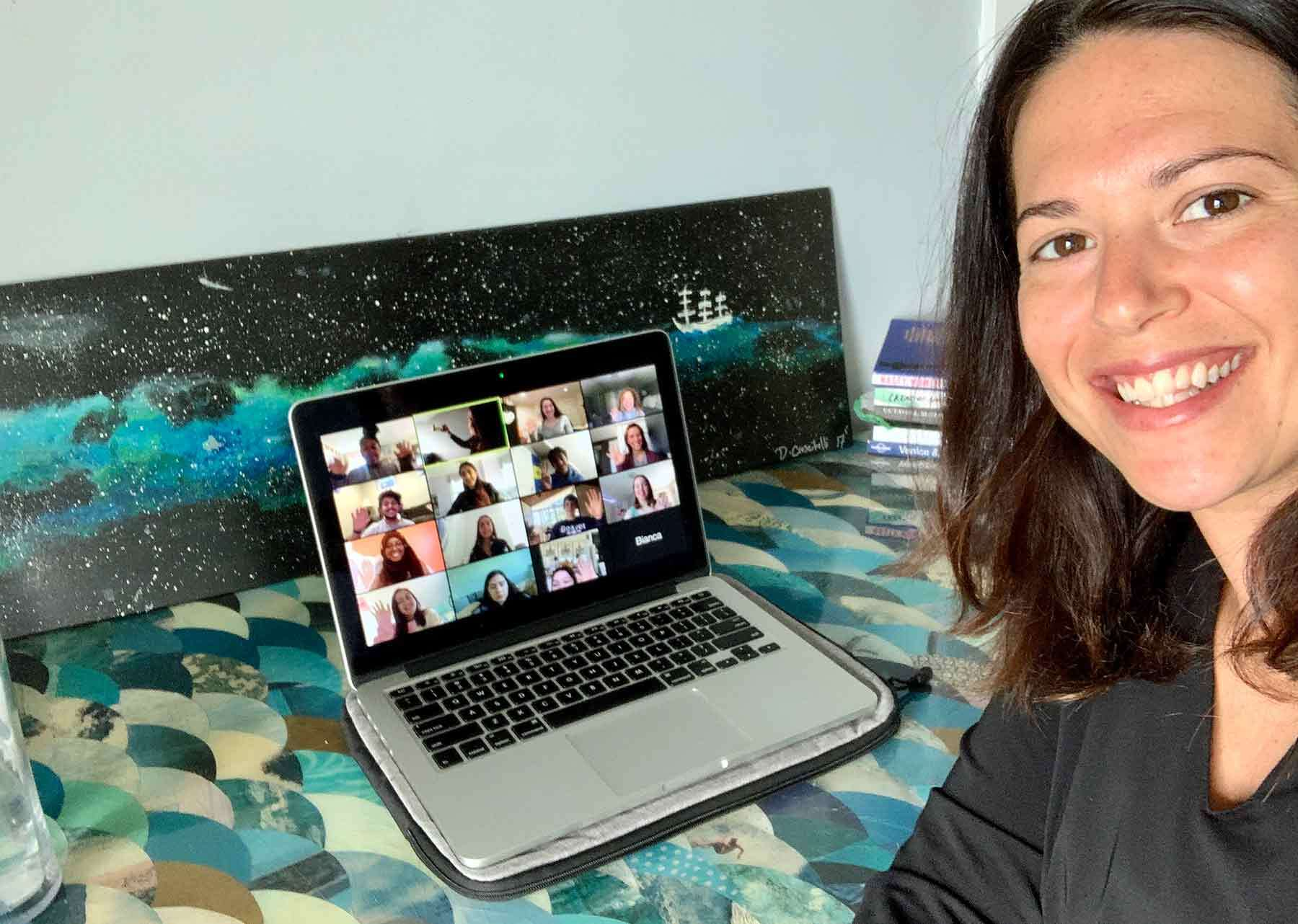 A smiling woman faces the viewer with a laptop full of students faces in a grid in the background