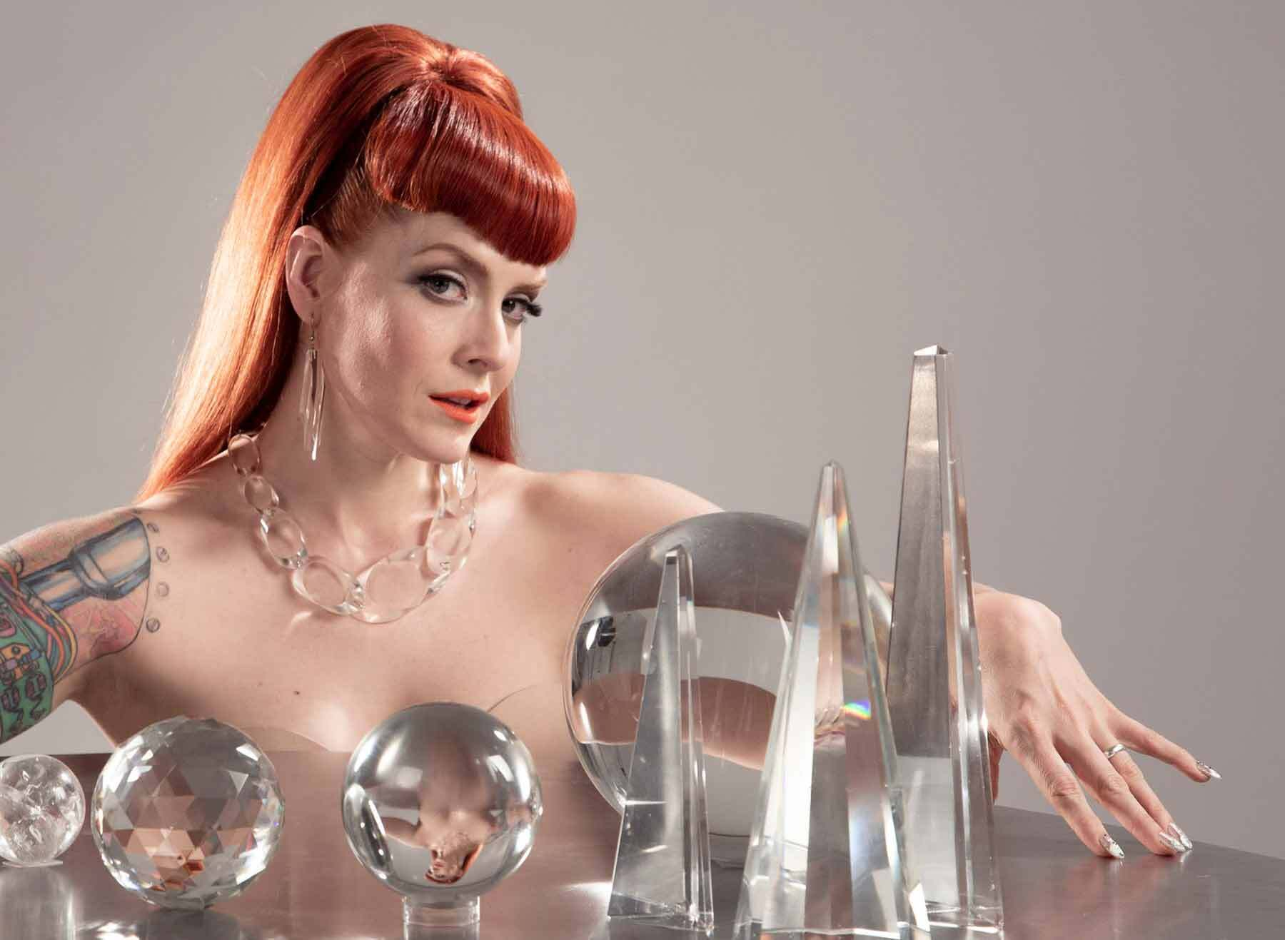 Ana Matronic, a red haired woman with her arm around glass balls and pyramids on a table.