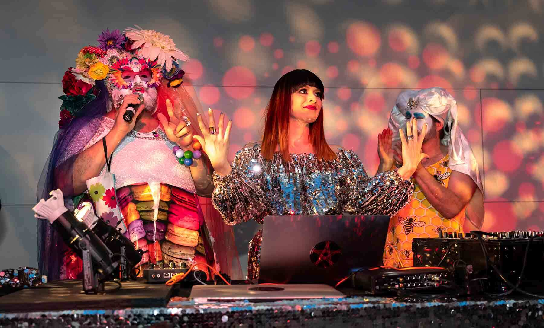 Three performers dressed in bright costumes perform as DJs in a brightly colored lit room.