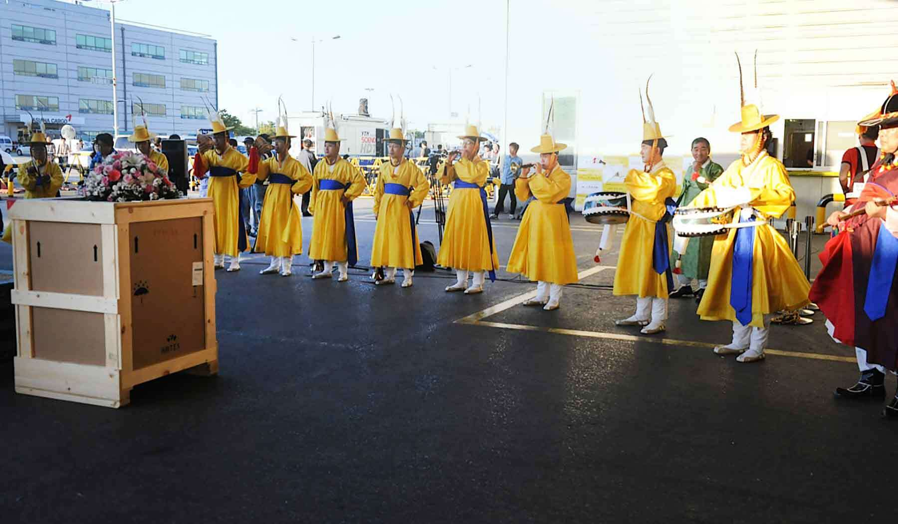 A large gathering of people in bright yellow dresses, some with drums give an official greeting an art object in a crate being offloaded from a truck at the airport.