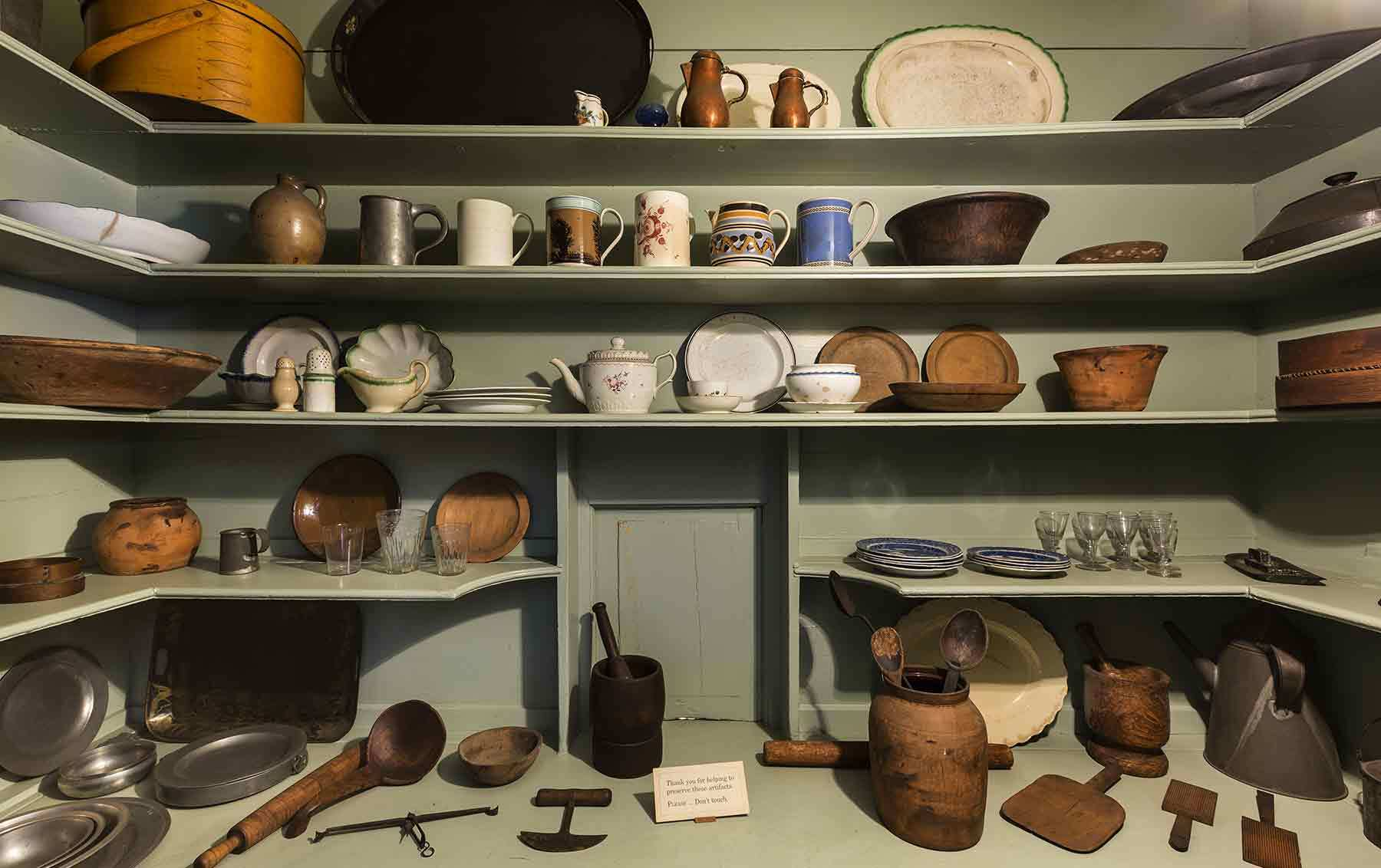 Interior of the Gardner-Pingree House, greyish green shelves with antique dishes on them