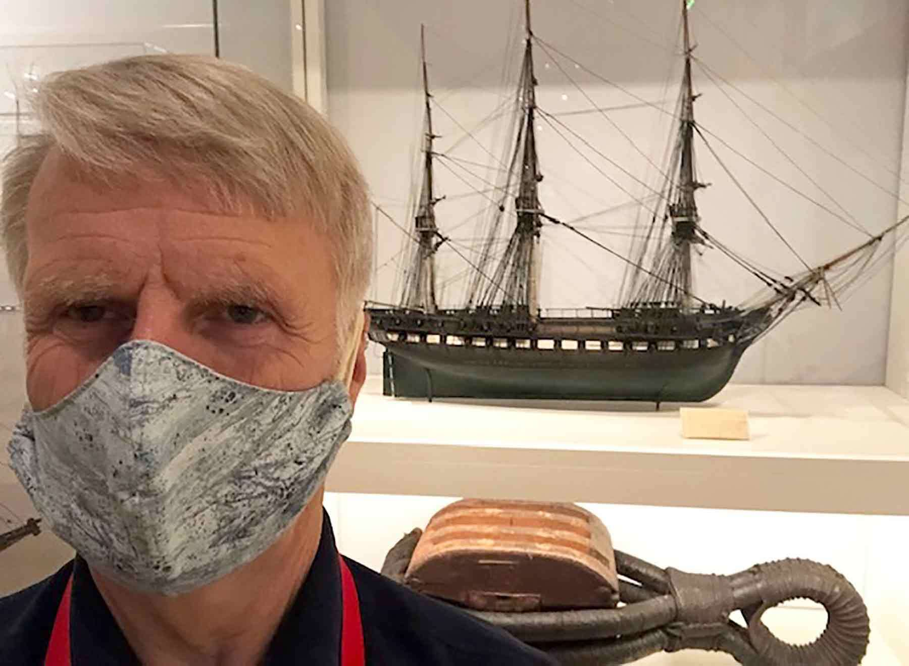 A close up of Bob Monk wearing a mask in front of a model ship in a gallery