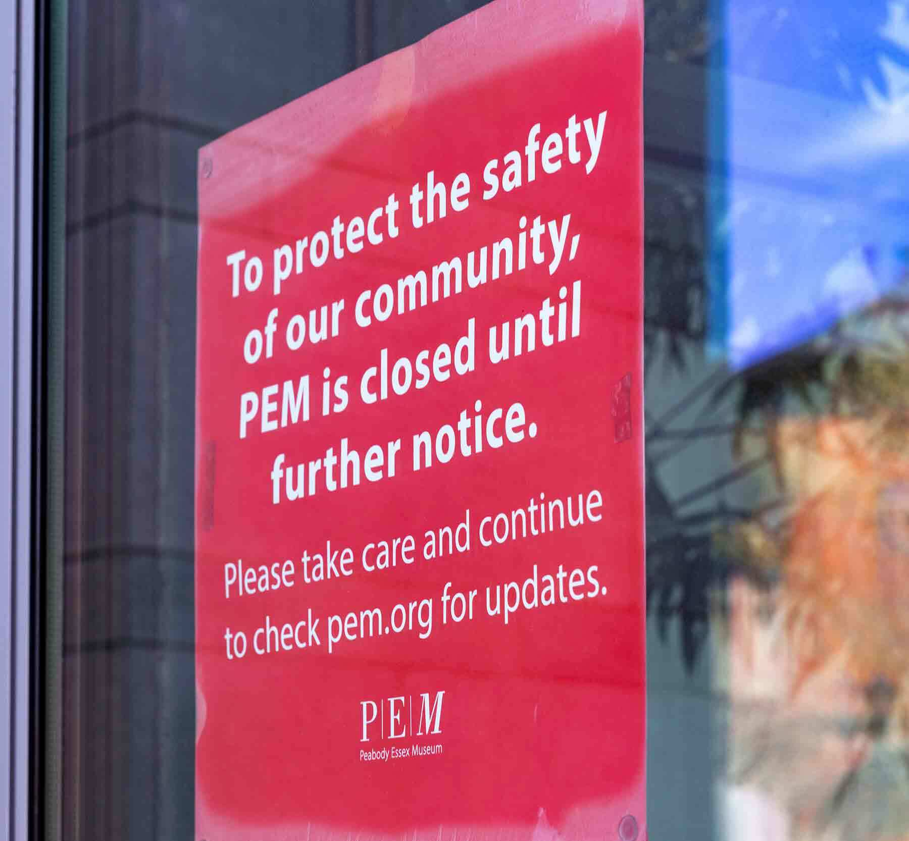 A red sign on a glass door that says PEM is closed temporarily