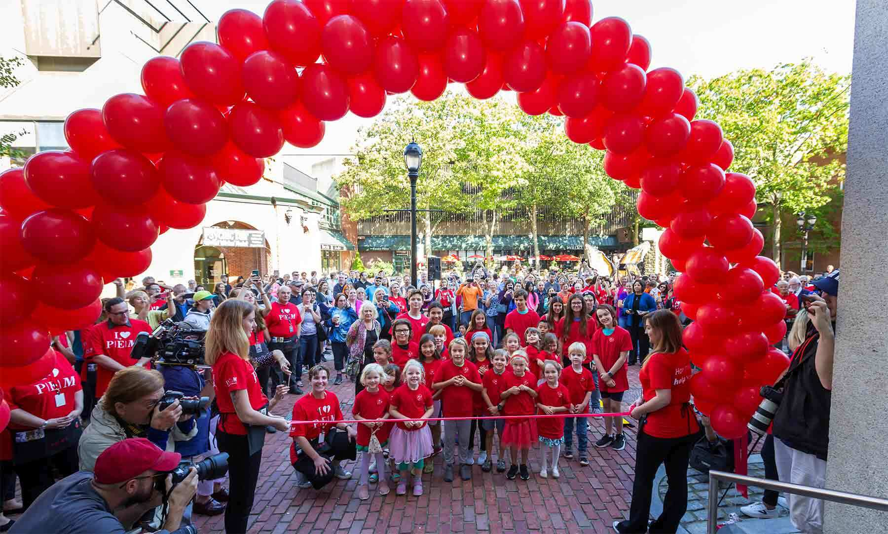 A crowd of people waiting to enter a building under a banner of red ballons