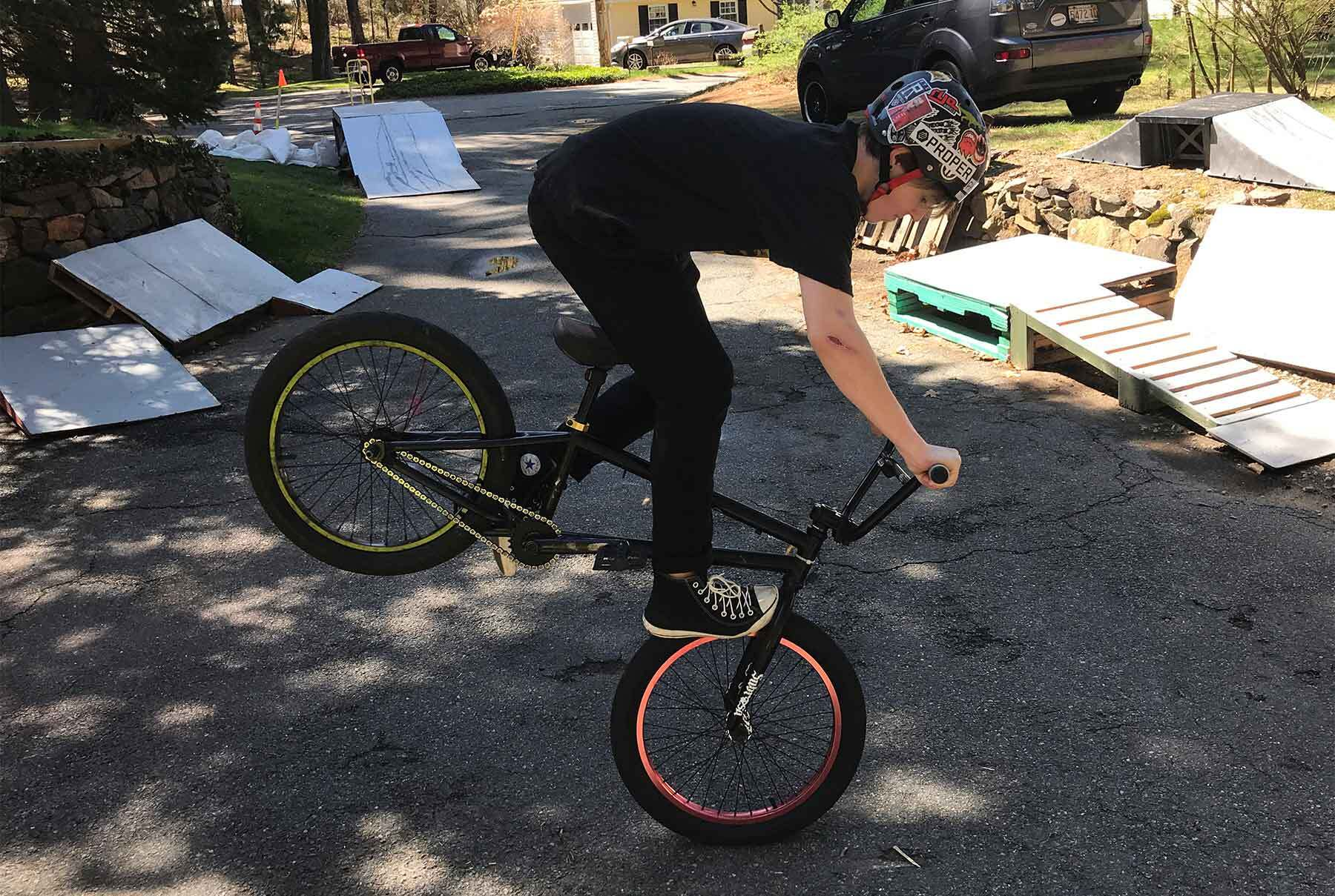 A boy wearing a helmet riding a BMX bike with the back wheel up in the air