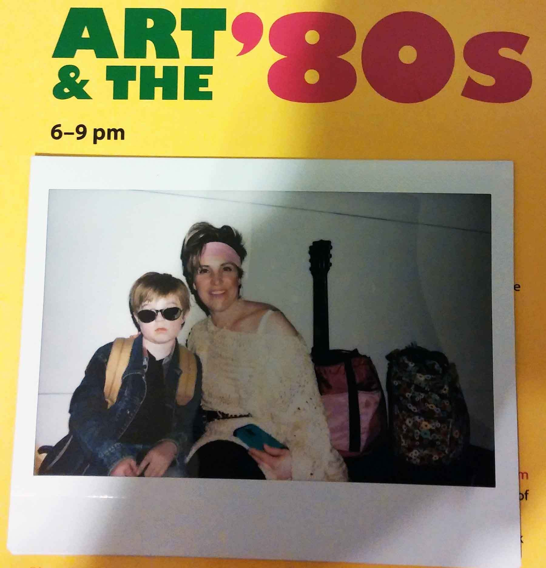"A woman and young boy in a polaroid photo ayyached to a yellow paper that has the words ""Art & the 80's"" painted on it"
