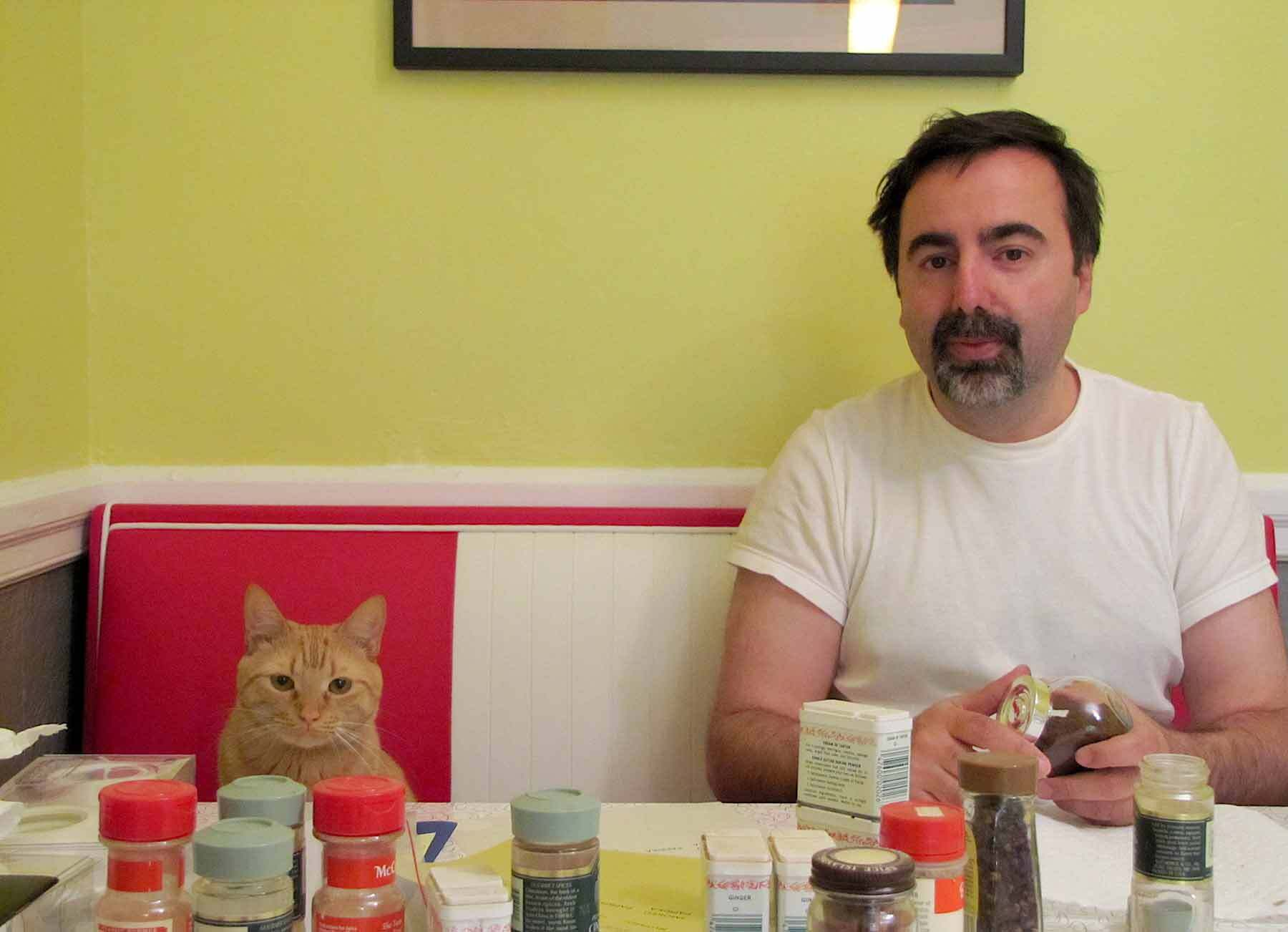 Abner the orange cat seated on a red bench at a table filled with spice jars, next to Victor.