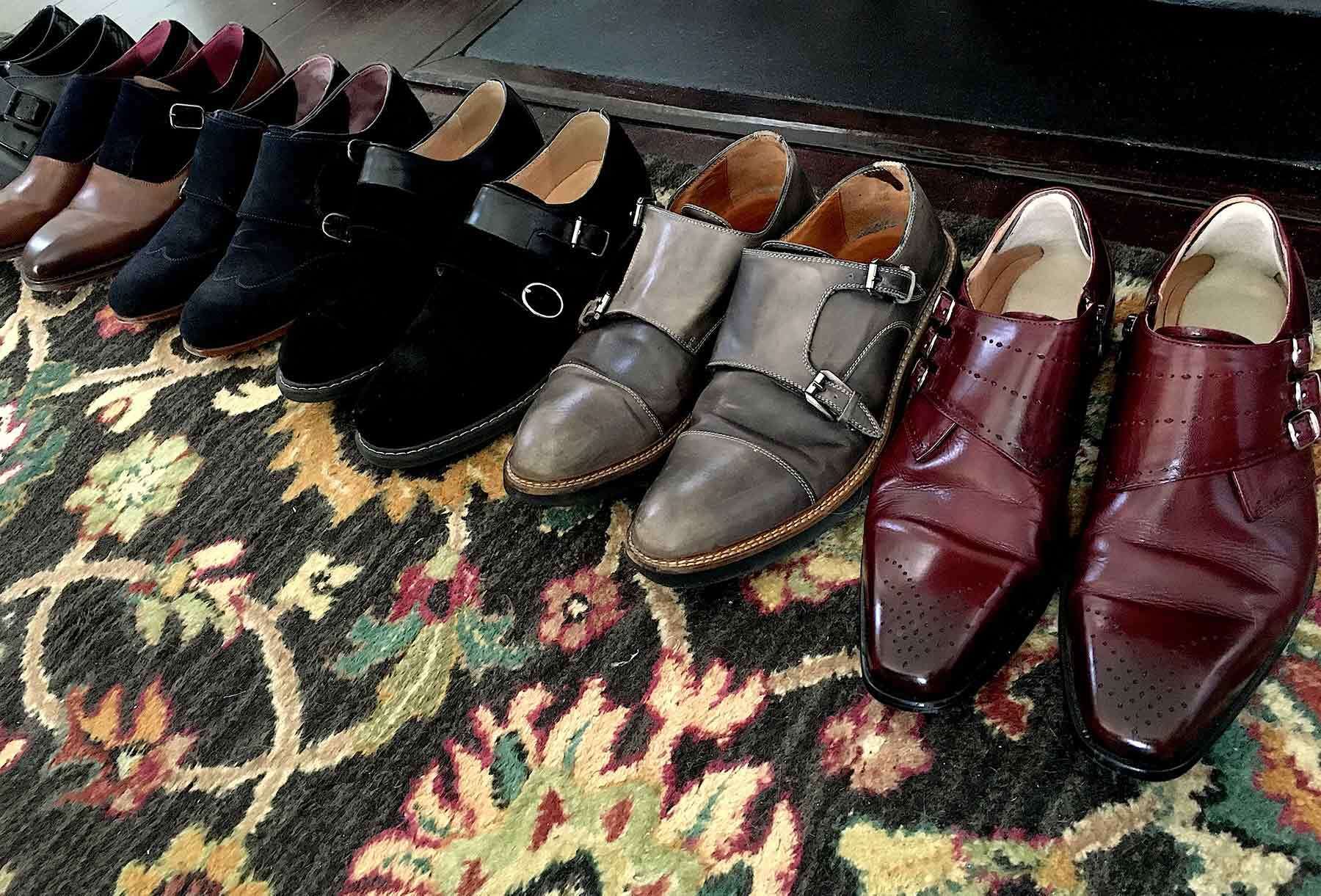 A row of mens shoes lined up on a flowery pattern rug